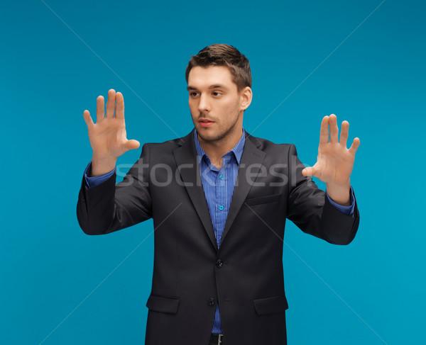Férfi öltöny dolgozik valami képzeletbeli kép Stock fotó © dolgachov