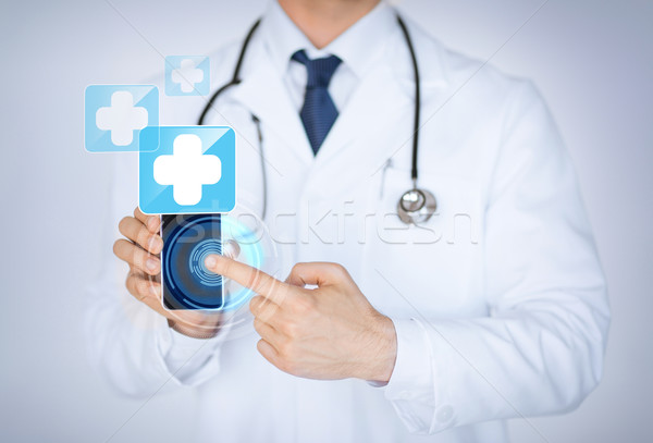 doctor holding smartphone with medical app Stock photo © dolgachov