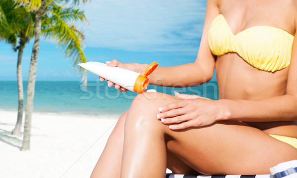 Stock photo: girl putting sun protection cream on beach chair