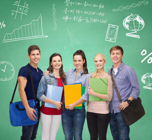 group of smiling students with folders and bags Stock photo © dolgachov