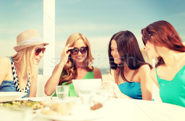 Stock photo: smiling girls looking at tablet pc in cafe