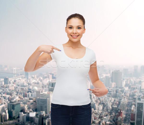 笑みを浮かべて 若い女性 白 Tシャツ ジェスチャー 広告 ストックフォト © dolgachov