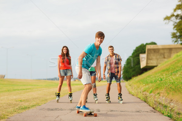 group of smiling teenagers with roller-skates Stock photo © dolgachov