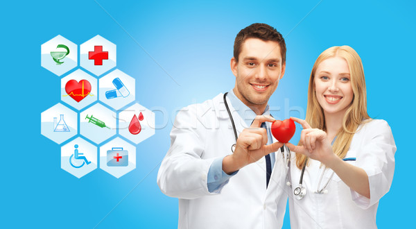 smiling doctors cardiologists with small red heart Stock photo © dolgachov