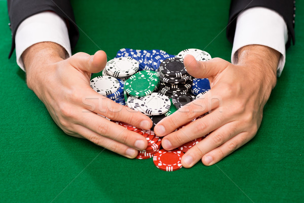 Stock photo: poker player with chips at casino table