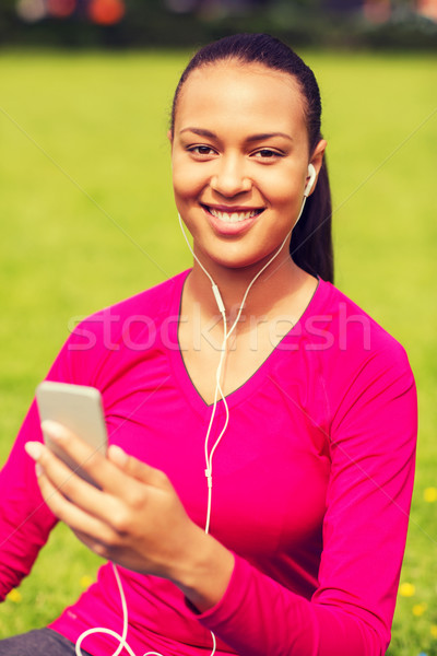 Stock photo: smiling african american woman with smartphone