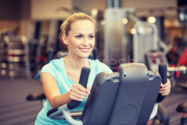smiling woman exercising on exercise bike in gym Stock photo © dolgachov