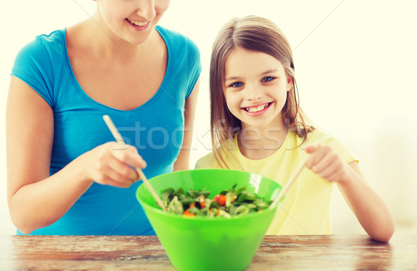 little girl with mother mixing salad in kitchen Stock photo © dolgachov