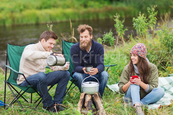 group of smiling tourists cooking food in camping Stock photo © dolgachov