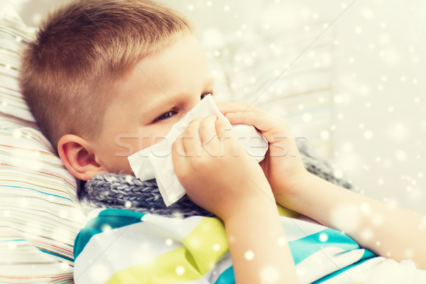 ill boy blowing nose with tissue at home Stock photo © dolgachov