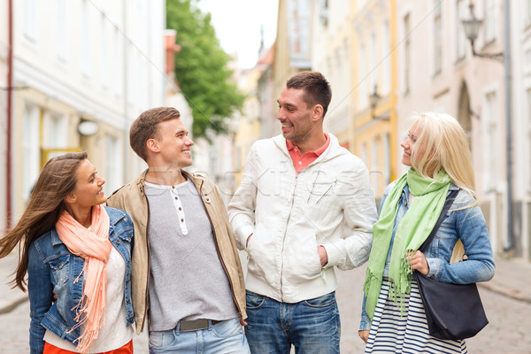group of smiling friends walking in the city Stock photo © dolgachov