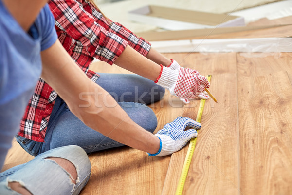 Stock photo: close up of couple with ruler measuring flooring