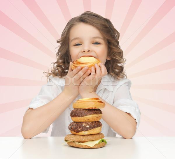 happy little girl eating junk food Stock photo © dolgachov