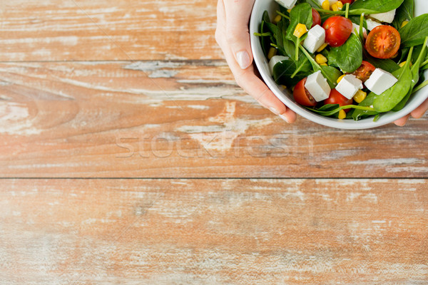 close up of young woman hands with salad bowl Stock photo © dolgachov