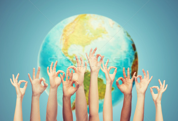 human hands showing ok sign over earth globe Stock photo © dolgachov