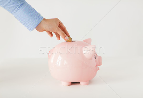 close up of hand putting coin to piggy bank Stock photo © dolgachov