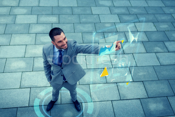 smiling businessman with virtual screens outdoors Stock photo © dolgachov
