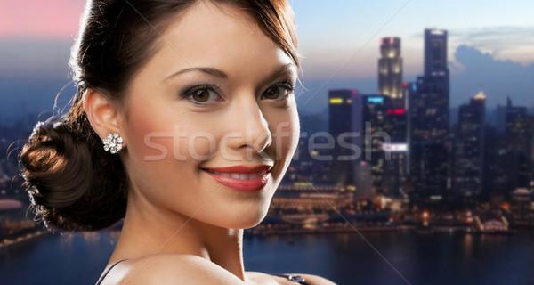 happy woman with diamond earring over night city Stock photo © dolgachov