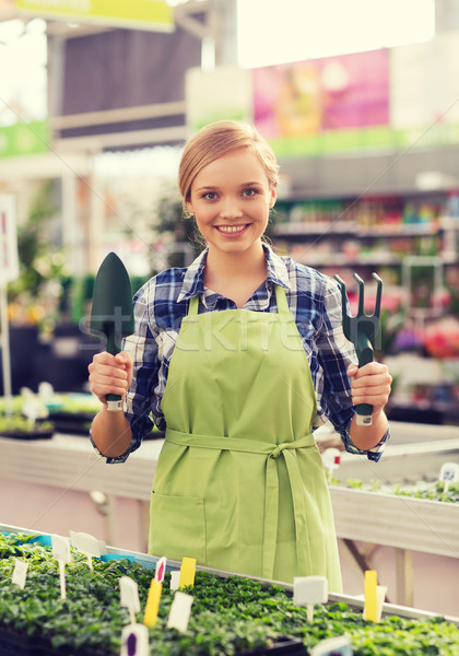 happy woman with gardening tools in greenhouse Stock photo © dolgachov
