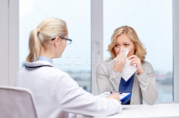 doctor and ill woman patient with flu at clinic Stock photo © dolgachov
