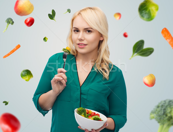 Stock photo: smiling young woman eating vegetable salad