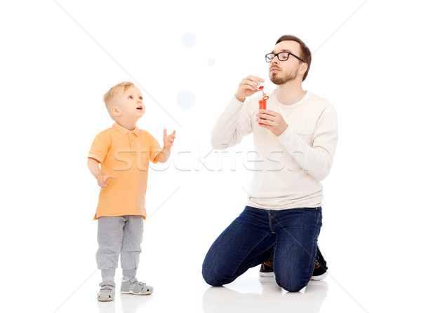 father with son blowing bubbles and having fun Stock photo © dolgachov