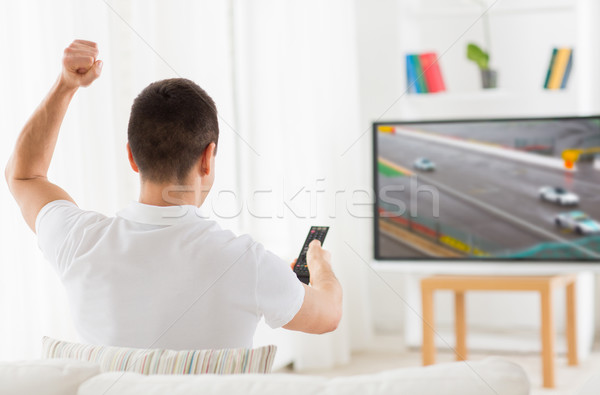 man with remote watching motorsports on tv at home Stock photo © dolgachov