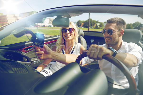 happy couple using gps navigator in cabriolet car Stock photo © dolgachov