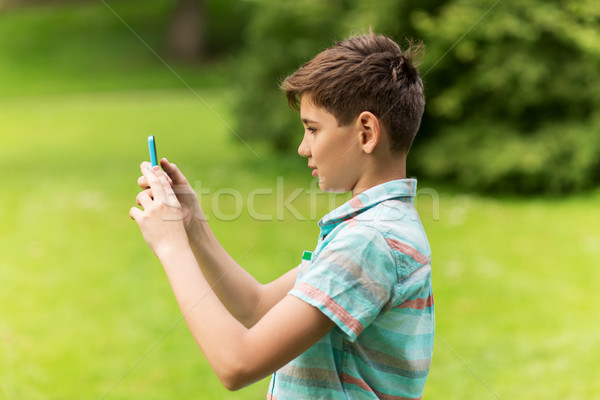 boy with smartphone playing game in summer park Stock photo © dolgachov