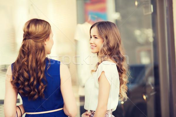 two happy women talking at shop window Stock photo © dolgachov