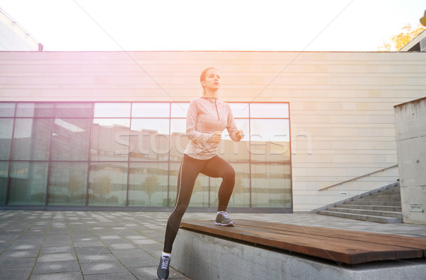 woman making step exercise on city street bench Stock photo © dolgachov