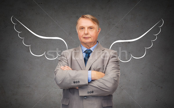 senior businessman with angel wings over gray Stock photo © dolgachov