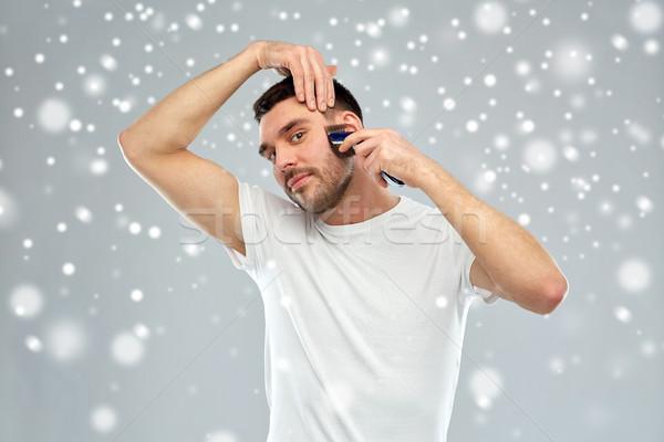 smiling man shaving beard with trimmer over snow Stock photo © dolgachov
