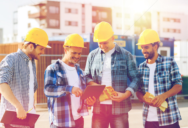 Stock photo: group of smiling builders with tablet pc outdoors
