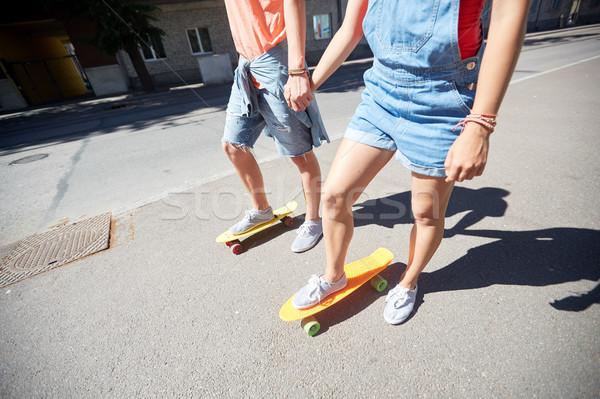 Stock photo: teenage couple riding skateboards on city street