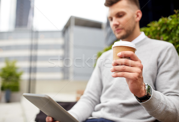 man with tablet pc and coffee cup on city street Stock photo © dolgachov