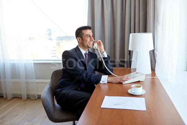 Empresário chamada secretária telefone quarto de hotel viagem de negócios Foto stock © dolgachov