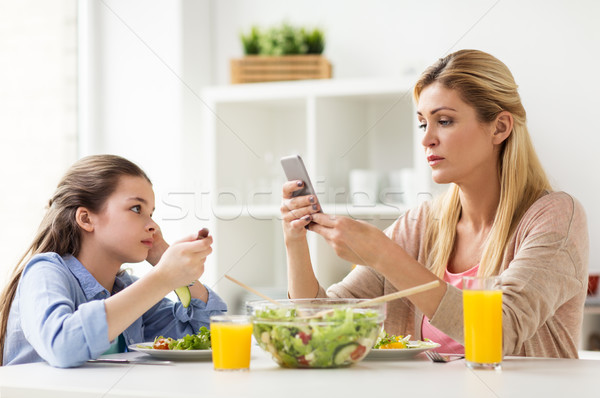 sad girl looking at her mother with smartphone Stock photo © dolgachov