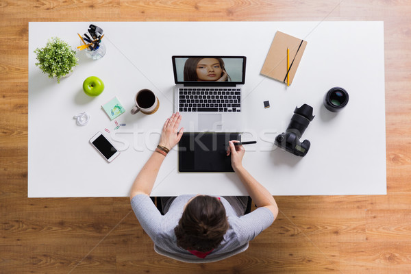 Stock photo: woman with camera working on laptop at table