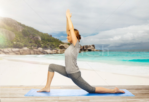happy woman doing yoga in low lunge on beach Stock photo © dolgachov