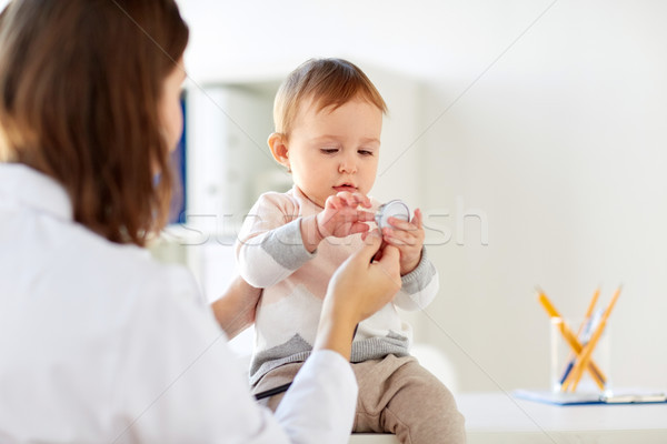 Stock photo: doctor with stethoscope and happy baby at clinic