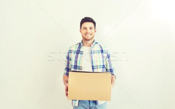 Sonriendo joven caja de cartón casa movimiento entrega Foto stock © dolgachov