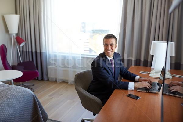 бизнесмен набрав ноутбука номер в отеле командировка люди Сток-фото © dolgachov