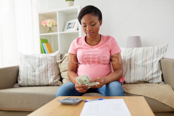 happy pregnant woman counting money at home Stock photo © dolgachov
