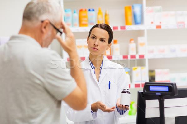 apothecary showing drug to senior man at pharmacy Stock photo © dolgachov