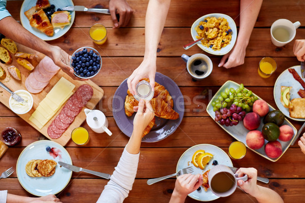 Stock photo: people having breakfast at table with food