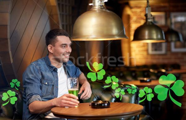 man drinking green beer at bar or pub Stock photo © dolgachov