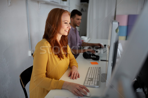 happy woman with computer working at office Stock photo © dolgachov