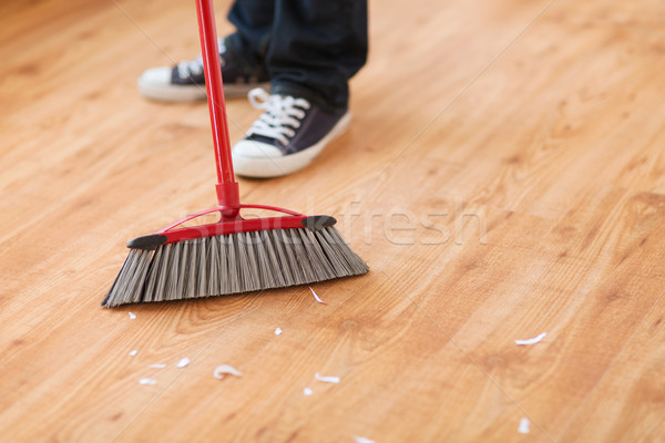 close up of male brooming wooden floor Stock photo © dolgachov