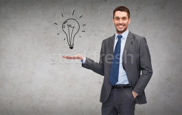 man showing light bulb on the palm of his hand Stock photo © dolgachov
